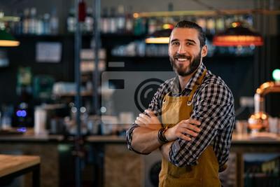Fototapeta Bartender wearing apron and smiling