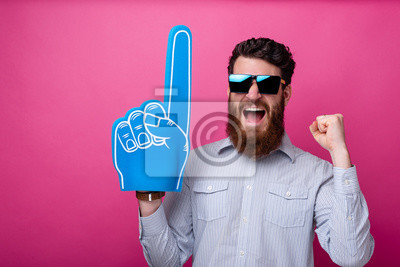 Fototapeta Bearded guy with big blue fan glove, screaming and support his team