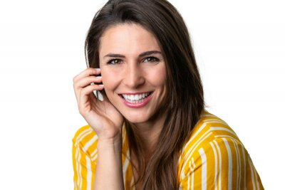 Fototapeta Beautiful brunette commercial model with perfect white teeth smile after visiting the dentist for tooth whitening
