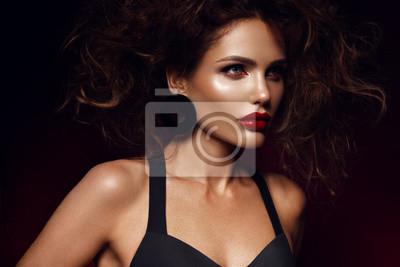 Fototapeta Beautiful face of a fashion model with red lips. Studio portrait.
