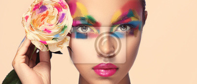 Fototapeta Beautiful girl model with multi-colored paints on her face. Woman with rose flower and bright color make-up. Cosmetics, beauty and makeup.  Spring and summer flowering  shopping