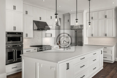 Fototapeta Beautiful kitchen in new luxury home with stainless steel appliances, pendant lights, and hardwood floors