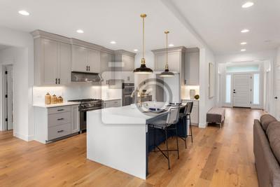 Fototapeta Beautiful kitchen in new luxury home with waterfall island, quartz counter tops, farmhouse sink, and hardwood floors.