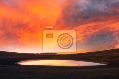 Beautiful landsckape. In the small volkanic lake reflected amazing sunset sky with beautiful orange clouds.
