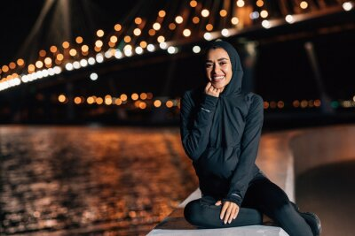 Fototapeta Beautiful middle east woman in hoodie sitting on embankment at night and resting after workout