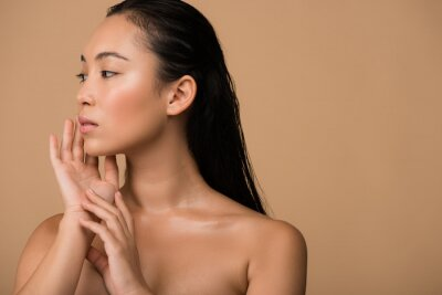 Fototapeta beautiful naked asian girl  looking away and touching face isolated on beige