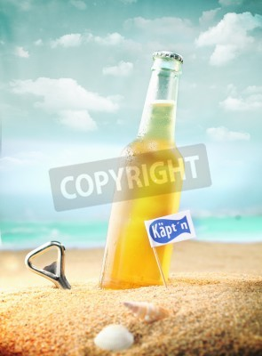 Fototapeta Beautiful photo of a chilled beer and a bottle opener on the beach tagged as Kapt'n.