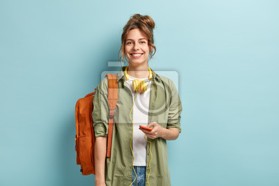 Fototapeta Beautiful smilig female traveller has leisure time, enjoys online communication, connected to headphones, listens music from playlist, wears casual white t shirt and green shirt, carries rucksack