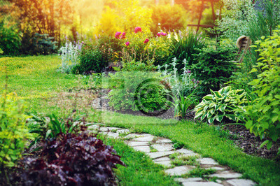 Fototapeta beautiful summer cottage garden view with stone pathway and blooming perennials