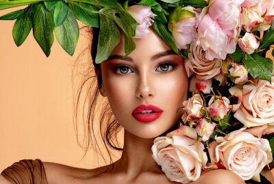 Fototapeta Beautiful white girl with flowers. Stunning brunette girl with big bouquet flowers of roses. Closeup face of young beautiful woman with a healthy clean skin. Pretty woman with bright makeup