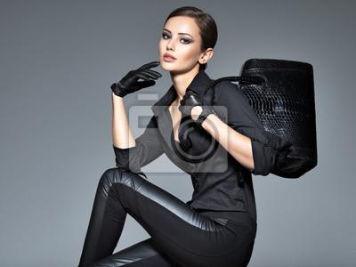 Fototapeta Beautiful woman in black  holds fashion handbag