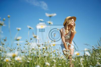 Fototapeta Beautiful woman in the field with flowers.