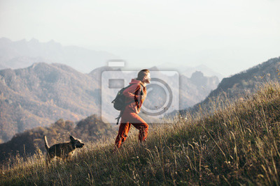 Fototapeta Beautiful woman traveler climbs uphill with a dog on a background of mountain views. She is with a backpack and in red clothes.