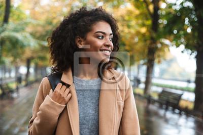 Fototapeta Beautiful young african woman wearing coat walking outdoors
