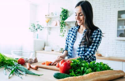Fototapeta Beautiful young woman is preparing vegetable salad in the kitchen. Healthy Food. Vegan Salad. Diet. Dieting Concept. Healthy Lifestyle. Cooking At Home. Prepare Food. Cutting ingredients on table
