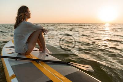 Fototapeta Beautiful young woman sitting on a stand up paddle board