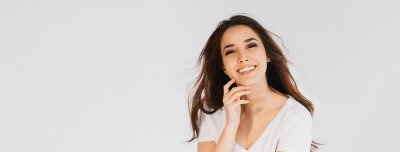 Fototapeta Beauty fashion portrait of smiling sensual asian young woman with dark long hair in white shirt on white background banner