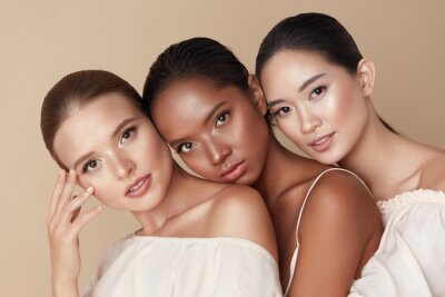 Fototapeta Beauty. Group Of Diversity Models Portrait. Multi-Ethnic Women With Different Skin Types Posing On Beige Background. Tender Multicultural Girls Standing Together And Looking At Camera.