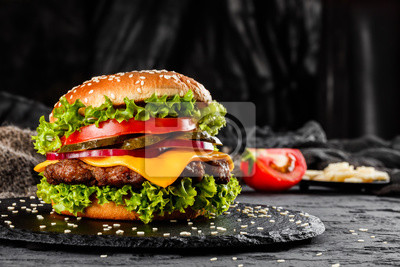 Fototapeta Beef burger with cheese, tomatoes, red onions, cucumber and lettuce on black slate over dark background. Unhealthy food