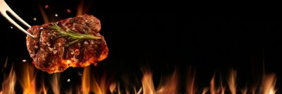 Fototapeta Beef steak falling on the grill with fire. Brazilian barbecue