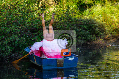 Fototapeta Behind view of a person in a small wooden boat on water making strange upside down positions in a funny dress