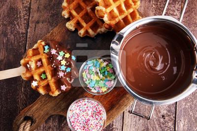 Belgijskie gofry z sosem czekoladowym. popsicles z czekoladą i wafelkiem.