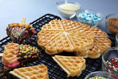 Belgium waffles with chocolate sauce. popsicles with chocolate and wafer on blue background