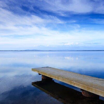 Fototapeta Betonowe molo lub molo i na niebieskim jeziorem i odbicie nieba.