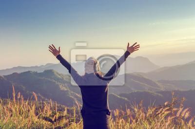 Fototapeta Beztroska szczęśliwa kobieta Cieszy się naturę na trawy łące na górze halnej falezy z wschodem słońca. Piękna dziewczyna plenerowa. Pojęcie wolności.
