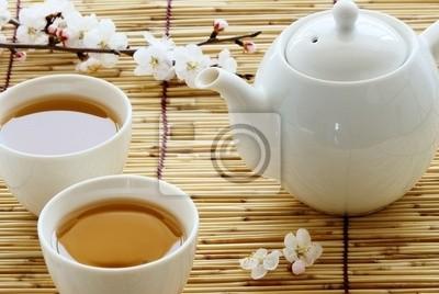 Biały kubek i czajnik na bambusowych słomek