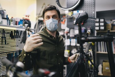 Fototapeta Bicycle mechanic wearing protective mask and gloves repairs customers bicycle wheel in accordance with quarantine standards during coronavirus pandemic. Small business during covid 19 lockdown
