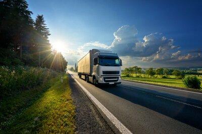 Fototapeta Biel ciężarówka przyjeżdża na asfaltowej drodze w wiejskim krajobrazie w promieniach zmierzch