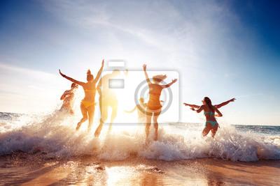 Fototapeta Big group happy friends runs and having fun at sunset beach