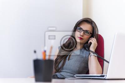 Biznes kobieta rozmawia przez telefon i za pomocą swojego laptopa