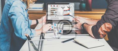 Fototapeta Biznesmen i businesswoman siedzi przy stole przed laptopem i pracy. Wykresy, diagramy i wykresy na ekranie komputera.