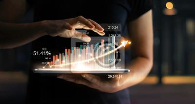 Fototapeta Biznesmena mienia pastylka i seans narastający wirtualny hologram statystyki, wykres i mapa z strzała up na ciemnym tle. Giełda Papierów Wartościowych. Koncepcja rozwoju, planowania i strategii biznes