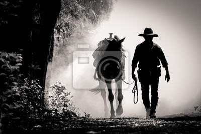 Fototapeta black and white picture silhouette of the cowboy and the horse in the morning sunrise