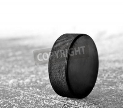 Fototapeta black hockey puck on ice rink