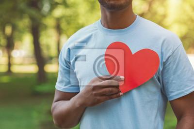 Fototapeta Black man holding red heart on his chest