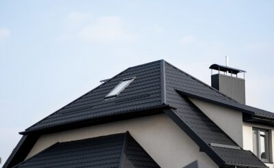 Fototapeta Black metal tile roof. Roof metal sheets. Modern types of roofing materials. Roof of the house, metal roof tile against the blue sky. Building.