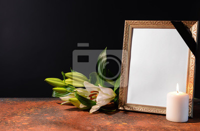 Fototapeta Blank funeral frame, candle and flowers on table against black background