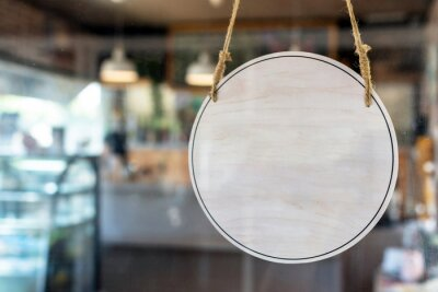 Fototapeta blank vintage wooden sign board hanging on glass door in modern cafe restaurant, copy space for text advertising, advertisement marketing and small business owner concept