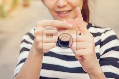 Fototapeta Bliska bandaż na palcu rannych podczas uśmiecha się, na zewnątrz w słoneczny wieczór
