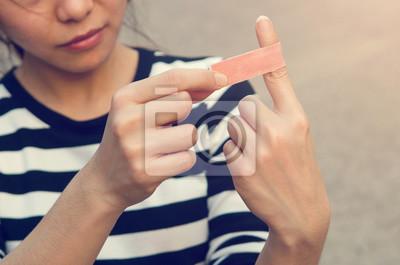 Fototapeta Bliska bandaż na rannych palcem, na zewnątrz.