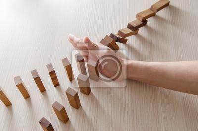 Fototapeta Bliska kobieta rękę zatrzymując domina drewniany efekt koncepcji biznesowych.
