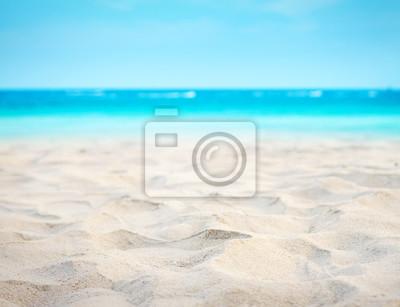 Fototapeta Bliska piasek z nieba tle niewyraźne morze, letni dzień, kopia przestrzeń lub do produktu.