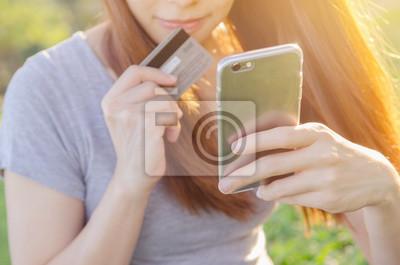 Fototapeta Bliska rąk za pomocą inteligentny telefon komórkowy i posiadania karty kredytowej na zewnątrz, zakupy online,