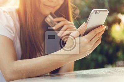 Fototapeta Bliska ręce posiadania karty kredytowej i przy użyciu telefonu inteligentnego telefonu na zewnątrz, zakupy, kobieta szczęśliwa.