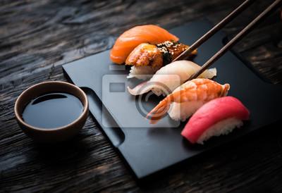 Fototapeta bliska sashimi sushi zestaw z pałeczkami i soi na czarnym tle