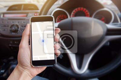 Fototapeta Bliska strony człowieka gospodarstwa inteligentny telefon komórkowy z aplikacją do nawigacji GPS na mapie. Niewyraźne wnętrza samochodu tła.